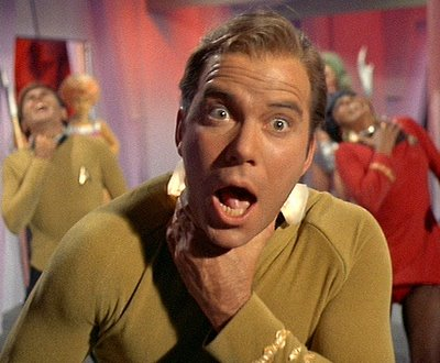 Captain Kirk (Shatner) in foreground, choking, as are Chekhov and Uhuru in background.